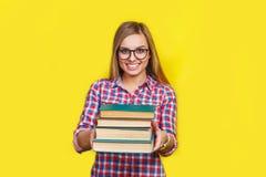El estudiante elegante joven sonriente se está colocando con los libros en fondo amarillo en vidrios y equipo brillante casual Imagen de archivo libre de regalías