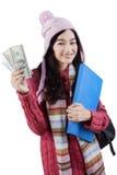 El estudiante en ropa del invierno sostiene el dinero Imagenes de archivo