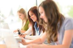 El estudiante en sala de clase usando el teléfono escribe el mensaje Imagen de archivo