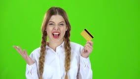 El estudiante en una blusa blanca con una tarjeta de crédito es feliz Pantalla verde metrajes