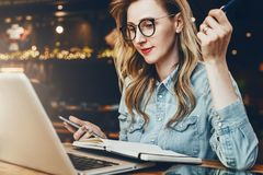El estudiante en vidrios de moda se sienta en café delante del ordenador portátil, mira webinar educativo Empresaria que trabaja  foto de archivo