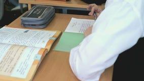 El estudiante escribe el texto en un cuaderno usando una pluma metrajes