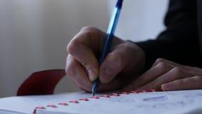 El estudiante escribe en su diario mientras que se sienta en una cama experiencias adolescentes 4K metrajes