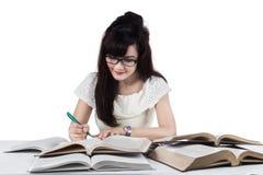 El estudiante escribe una fuente en el libro Fotografía de archivo libre de regalías