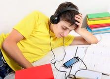 El estudiante escucha la música Foto de archivo