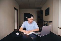 El estudiante estudia en casa El adolescente mira el ordenador y escribe el texto al cuaderno fotos de archivo