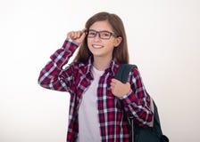 El estudiante feliz con la mochila está permaneciendo en el fondo blanco De nuevo a universidad foto de archivo libre de regalías