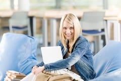 El estudiante feliz joven de la High School secundaria se relaja con la computadora portátil Fotografía de archivo
