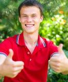 El estudiante feliz joven está mostrando el pulgar encima de la muestra Fotografía de archivo
