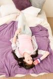El estudiante feliz joven relaja la mentira en cama Foto de archivo libre de regalías
