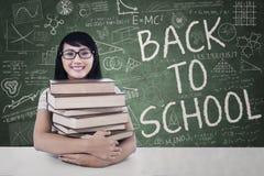 El estudiante feliz sostiene los libros de texto en clase Foto de archivo libre de regalías
