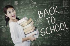 El estudiante feliz sostiene los libros de texto en la clase 1 Fotos de archivo libres de regalías