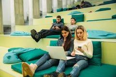 El estudiante feliz tiene una rotura en universidad Tenga un buen rato mientras que usa el teléfono, la tableta y el ordenador po Imagenes de archivo