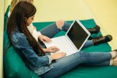El estudiante feliz tiene una rotura en universidad Tenga un buen rato mientras que usa el teléfono, la tableta y el ordenador po Fotos de archivo libres de regalías