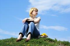 El estudiante femenino al aire libre encendido gren la hierba con los libros Fotos de archivo libres de regalías
