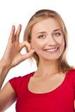 El estudiante femenino atractivo en rojo muestra OK Fotos de archivo libres de regalías