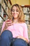 El estudiante femenino bonito escucha la música Foto de archivo libre de regalías
