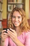 El estudiante femenino bonito lee un mensaje de texto Imágenes de archivo libres de regalías