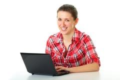 El estudiante femenino feliz en camisa roja trabaja en la computadora portátil Imagen de archivo