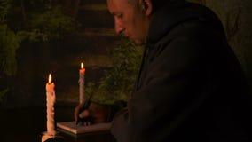 El estudiante hace la preparación en la noche con las velas Escritura del estudiante en cuaderno con la pluma en la noche oscura