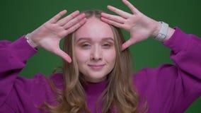El estudiante hermoso del jengibre hace los movimientos extraños de la danza en fondo verde de la croma metrajes