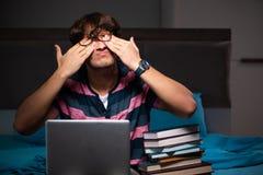 El estudiante hermoso joven que se prepara para los exámenes en la noche foto de archivo