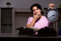 El estudiante hermoso masculino que se prepara para los exámenes tarde en casa imagen de archivo