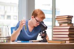 El estudiante joven cansó y agotó la preparación para el examen de la química imagenes de archivo
