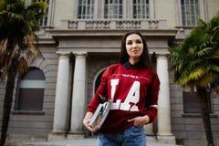 El estudiante joven con Asia se coloca en el fondo de la universidad Foto de archivo