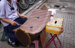 El estudiante joven con el tambor uniforme del juego pega el pulso del xylopho Foto de archivo libre de regalías