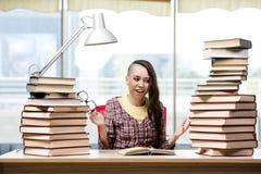 El estudiante joven con la pila de libros Foto de archivo libre de regalías
