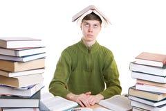 El estudiante joven con los libros aislados en un blanco Imagen de archivo libre de regalías