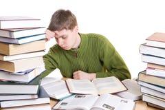 El estudiante joven con los libros aislados en un blanco Foto de archivo libre de regalías