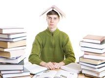 El estudiante joven con los libros aislados en un blanco
