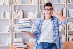 El estudiante joven con los libros que se preparan para los exámenes Foto de archivo