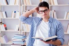 El estudiante joven con los libros que se preparan para los exámenes Imagen de archivo
