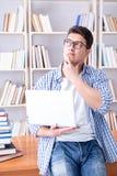 El estudiante joven con los libros que se preparan para los exámenes Foto de archivo libre de regalías
