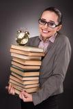 El estudiante joven con los libros y el reloj Imagen de archivo
