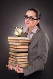 El estudiante joven con los libros y el reloj Imagen de archivo libre de regalías
