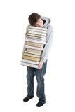 El estudiante joven con una pila de libros aislados Foto de archivo libre de regalías