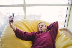 El estudiante joven del inconformista que se sienta en un bolso de la silla y hace el selfie Silla cerca de la ventana Hombre en  Fotos de archivo libres de regalías