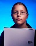 El estudiante joven en vidrios sostiene la carpeta Fotos de archivo