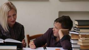 El estudiante joven enganchó a las lecciones con su profesor helping
