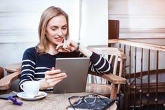 El estudiante joven está mirando película en la tableta digital mientras que se sienta en el café, mujer hermosa que usa COM del  Imagen de archivo libre de regalías