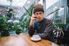El estudiante joven feliz en vidrios habla por el teléfono y bebe el té que pasa por alto la terraza con las plantas verdes Fotografía de archivo libre de regalías