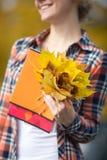 El estudiante joven femenino atractivo sonriente al aire libre que lleva a cabo amarillo se va Fotografía de archivo libre de regalías
