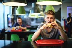 El estudiante joven hermoso come una hamburguesa en un restaurante de los alimentos de preparación rápida Comida sabrosa y dañina Foto de archivo