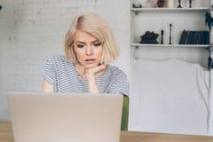 El estudiante joven hermoso se sienta delante de un ordenador portátil Fotografía de archivo