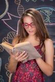 El estudiante joven lee el libro delante de la pizarra de la escuela Fotografía de archivo libre de regalías