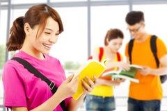El estudiante joven leyó un libro con los compañeros de clase en la escuela Fotografía de archivo libre de regalías